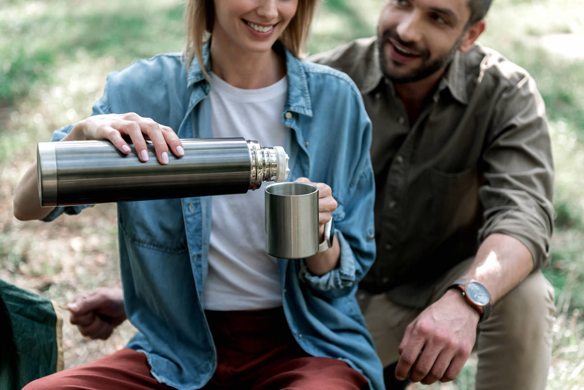 Cheerful couple is resting in the nature together. They are sitting and laughing. Focus on female hands pouring hot beverage from thermos into mug