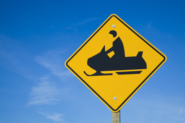 Careful! Snowmobiles! - road sign against blue sky.
