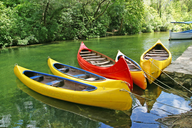 Five empty plastic canoes in turquoise green river